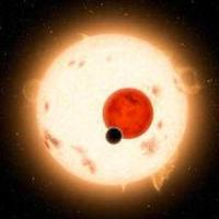 A large sun shines behind a red planet and a smaller black planet in space