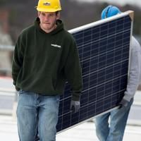 Workers walking with a solar panel