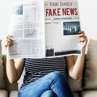 "woman on couch holding up newspaper with giant headline that says ""Fake News"""