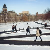 students walk across the arts quad in winter