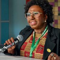 N'Dri Thérèse Assié-Lumumba speaking with a microphone