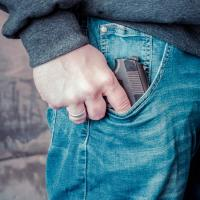 Hand touching gun in jeans pocket