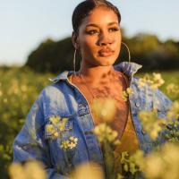 Black woman standing in field of flowers