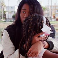 """Black woman hugging her daughter in a scene from """"From Land to Land"""" film"""