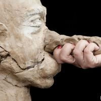 Hand grasping clay nose of bust of a man