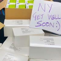 "Boxes of donations with a sign saying ""NY Get Well Soon"""
