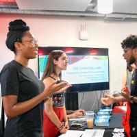 Students from Blackstone LaunchPad explain their resources during an entrepreneurship fair