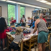 Alumni and families gather around a table with hyperbolic crochet examples and books