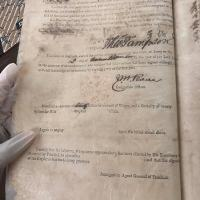 gloved hand holding an antique document
