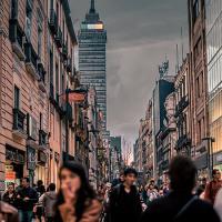 City street full of people; dark sky