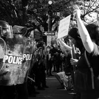 A line of police with shields stands against protesters