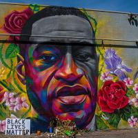 Artist drawing of George Floyd's face on a wall, surrounded by flowers and Black Lives Matter sign