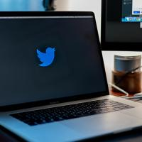 Laptop showing blue bird Twitter logo on a black screen