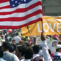 """Image of a rally with an American flag and a sign saying """"love"""""""