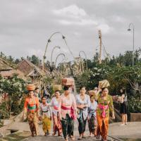 Women wearing brightly colored clothes walking in a village with baskets on their heads.