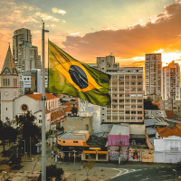 Brazilian flag with city and sunset in background