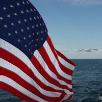 US Flag flying over the ocean