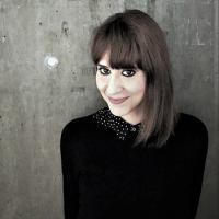 Valeria Dani - a woman in a black sweater before a gray, concrete background.