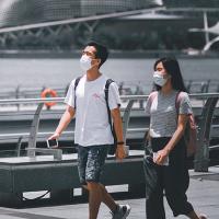 Two people walking, wearing masks