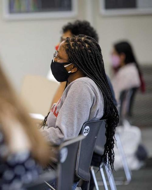 Masked student in class