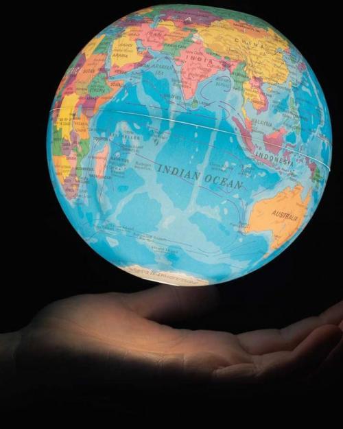 glowing earth globe, human hand