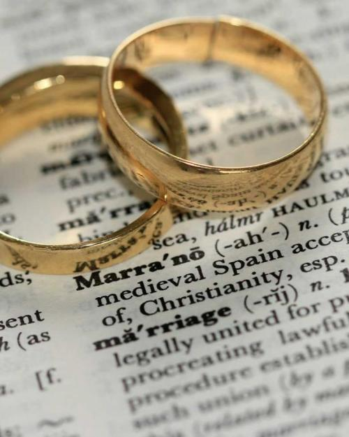 Two gold rings on a dictionary definition of 'marriage'