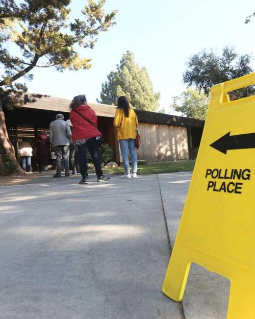 """Yellow """"polling place"""" sign and voters"""