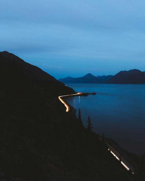 Highway with lights snakes between mountain and bay