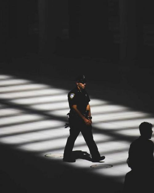 person in polic uniform, walking through shadowy space