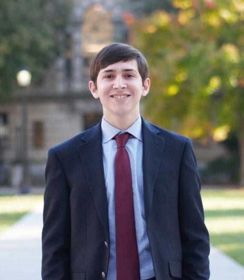 Adam Herold in a suit in front of an academic building.