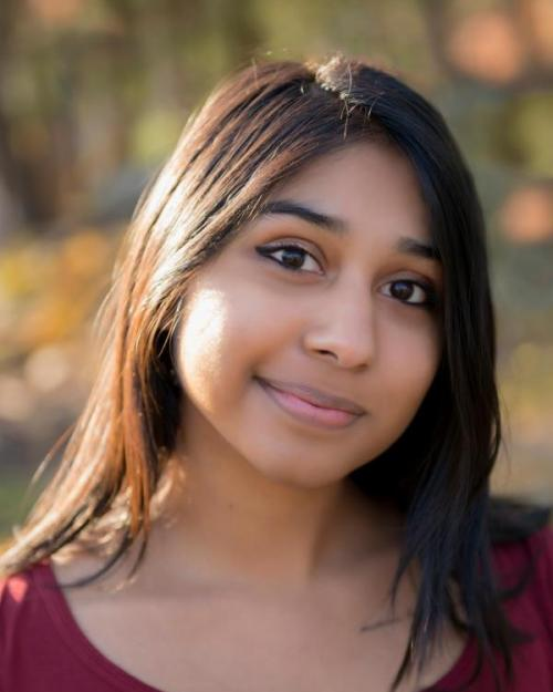 Alyssa Kamath portrait photo with fall colors in the back.
