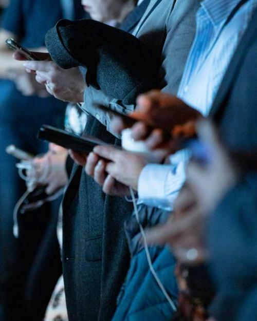 people in business clothes check smart phones