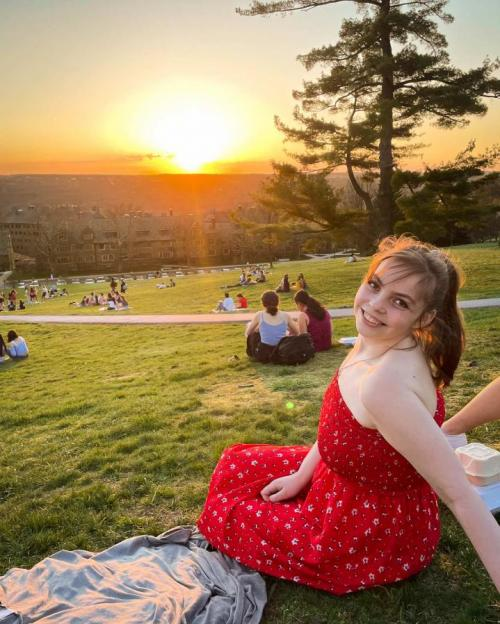 girl on slope of hill during sunset