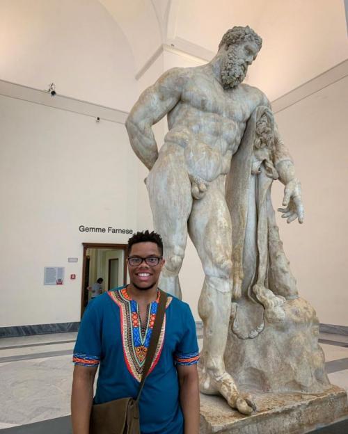 man by Greek statue