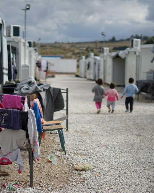 Three children walk away down a path between tents