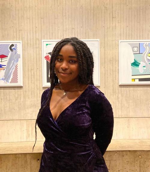 Lauren Thomas standing in an art exhibit.