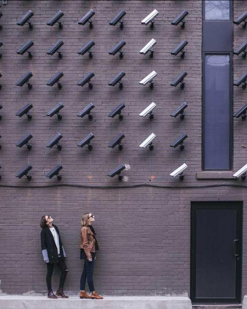 Two people face many security cameras