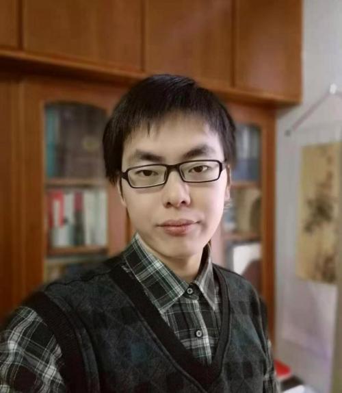 Zhiyuan Zhou in front of a book case.