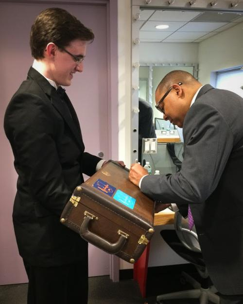 student getting instrument signed by Wynton Marsalis