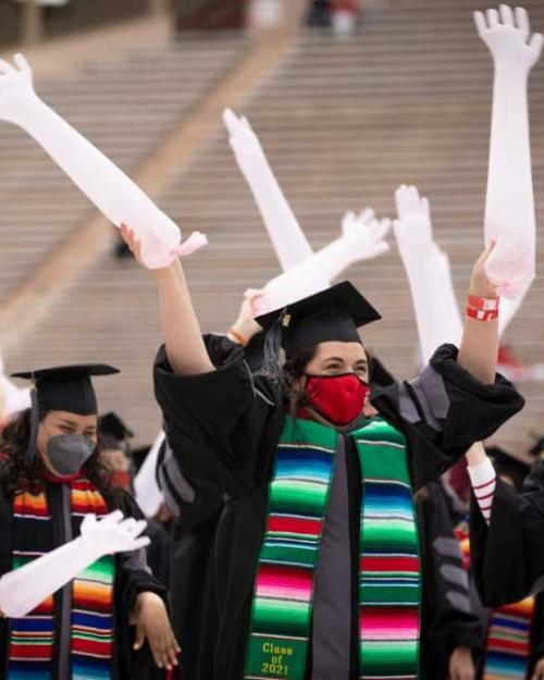 People in graduation caps and gowns wave balloons