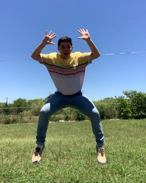 Student smiling while jumping