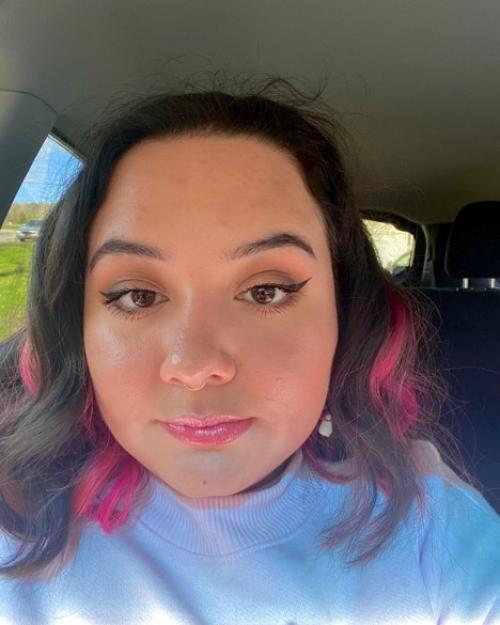 Student with black and pink hair sitting in a car