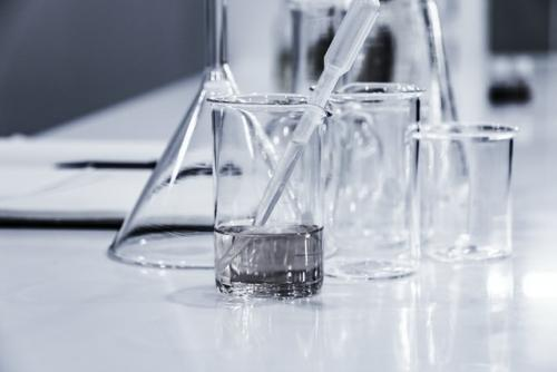Glass beakers on a table, one partially filled with liquid