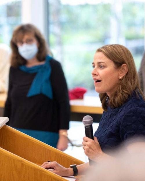 Dean Colleen Barry with microphone in hand, speaking at podiumSchool of Public Policy