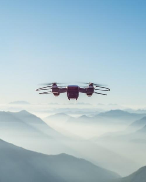 Drone flying in the air with mountains in the background