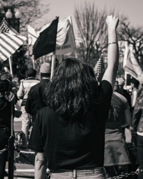 A woman standing with her fist upraised at a protest at the White House