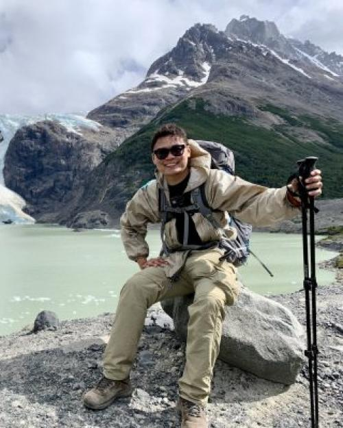Ngoc Truong sitting on a rock in front of a lake and a mountain with glacier