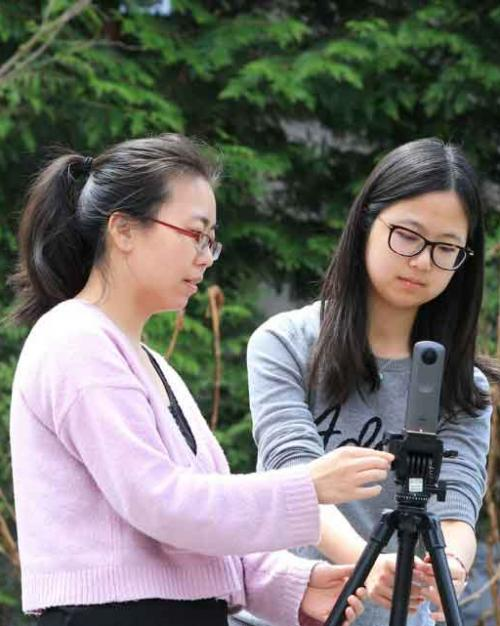 two students with video camera