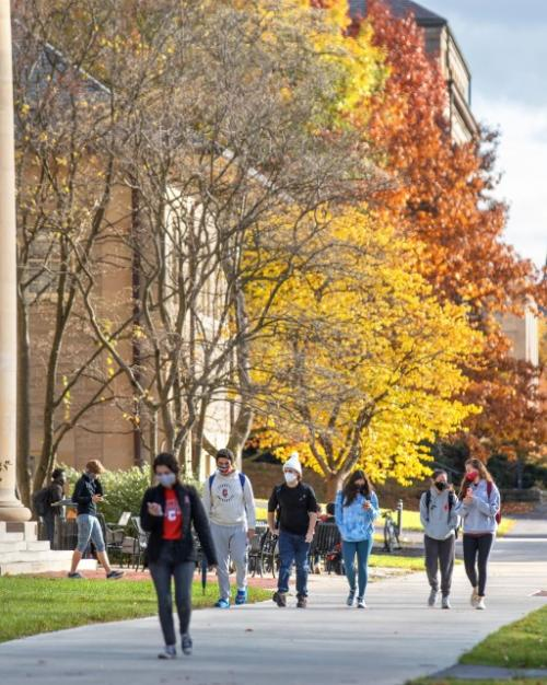 Students walking in front of Goldwin Smith Hall, with trees showing Autumn colors