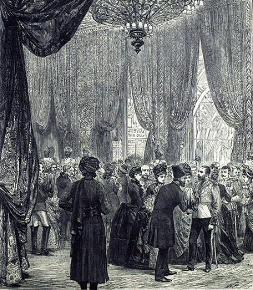 Image of a ball in colonial India, with a chandelier; men and women in fancy evening clothes, and Indians in turbans